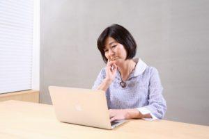 パソコンの画面を見て困った表情をする中年女性