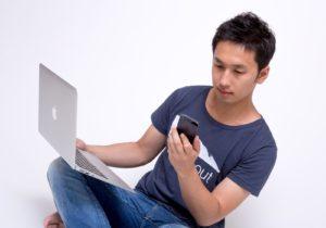 ノートパソコンとスマートフォンを同時に操作する個人事業主